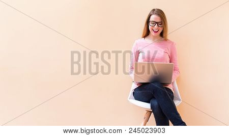 Happy Young Woman Using Her Laptop Computer At Home