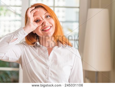 Redhead woman wearing white shirt at home with happy face smiling doing ok sign with hand on eye looking through fingers