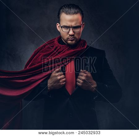 Portrait Of A Genius Superhero In A Black Suit With A Red Tie. Isolated On A Dark Background.