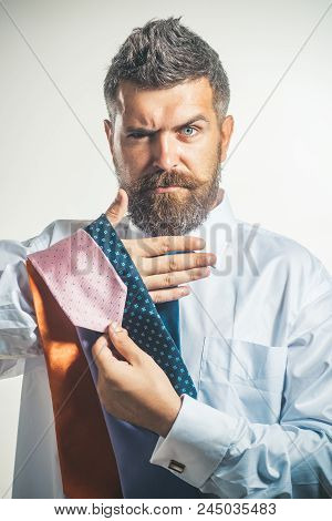 Fashion, Business, Clothing And People Concept - Serious Gentleman Chooses Necktie. Confidence Succe