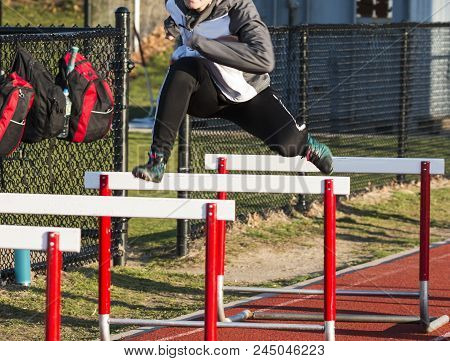 A Track And Field Female Hurdler Is Actively Warming Up Over Hurdles Wearing A Sweatsuit To Stay War