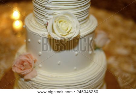 Lighting The Way: White Triple-layered Wedding Cake Decorated With Roses
