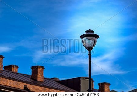 One Street Electric Lamppost Against The Background Of The Rooftop And The Evening Sky