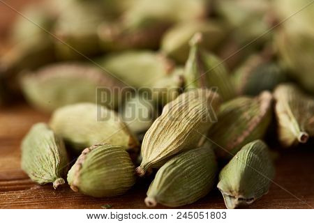 Close-up Of Green Cardamon Seeds On Rustic Wooden Background, Top View, Selective Focus, Shallow Dep