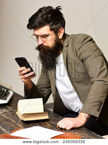 Bearded Man In Reading Glasses With Smartphone. Scientist Hipster With Mobile Phone And Book. Busine