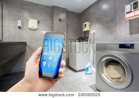 mobile phone with smart home app in modern washhouse; laundry