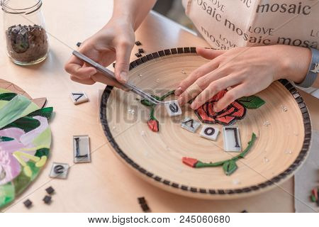 Workplace Of A Mosaic Master: Female Hands Laying Out A Mosaic Element On The Table. Master Lays The