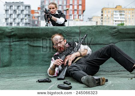 Man And Woman Dressed As Special Agnets Or Killers With Rifles On The Roof Of The House Keep The Vic