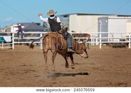 A Cowboy Competing In A Bull Riding Competition At A Country Rodeo