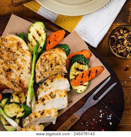 Grilled Chicken Breasts With Grilled Vegetables Zucchini And Carrot Background. Selective Focus.