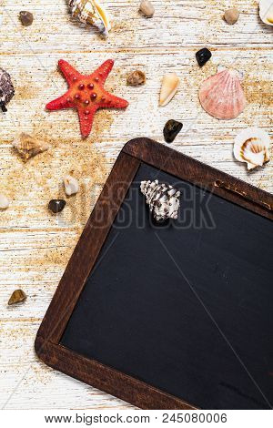 Top View Of Beach Sand, Shells And Starfish With Black Chalkboard Background Card Concept. Selective