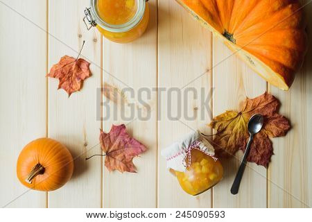 Top View Of Autumn Still Life Of Organic Pumpkin, Pumpkin Jam In A Jar, Maple Leaves And Spoon On Na