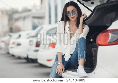 Beautiful Brunette Young Woman With Shopping Bag Near The White Super Car, Outdoors. Woman Standing