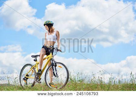 Beautiful Woman Cyclist Posing With Yellow Mountain Bike On A Grass, Wearing Helmet, Enjoying Summer