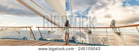Luxury cruise ship vacation woman on deck banner panorama. Travel in Tahiti on sail boat, exotic destination. Tourism in oceania. Boat sailing away on tropical getaway
