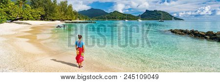 Travel tourist woman at French Polynesia beach on Huahine island cruise excursion on Tahiti holiday vacaton. Girl wearing polynesian sarong skirt banner panorama crop.