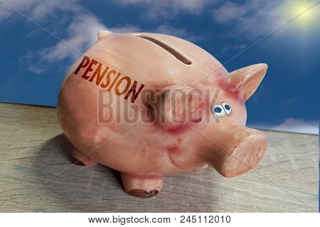 Piggy Bank, Good Luck Pig With Lettering Pension On Wooden Surface In Front Of Blue Sky Background