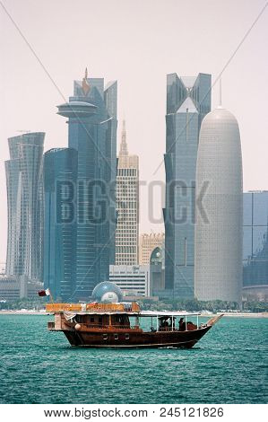 DOHA, QATAR - May 6, 2018: A traditional wooden dhow sails in front of some of Qatar's skyscrapers in Doha Bay. Film photo with grain.