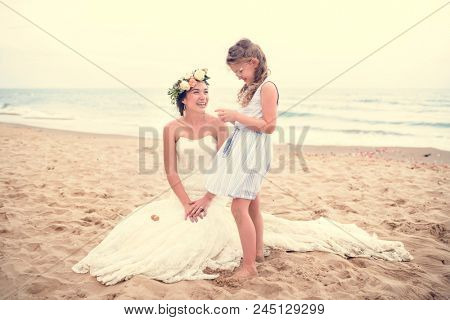 Beautiful bride and sister by the sea