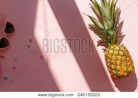 Juicy Pineapple And Pink Sunglasses On Trendy Pink Paper Background In Sun Light. Flat Lay. Creative