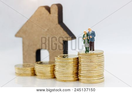 Miniature People: Happy Senior Couple Standing On Coins Stack With House, Money Saving Growth. Retir