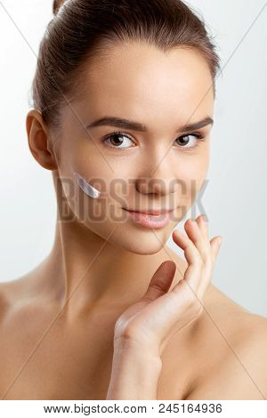 Beauty Skin Care. Beautiful Happy Woman Applying Cosmetic Cream On Clean Face. Closeup Portrait Of H