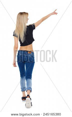 Back view of a girl walking with a pointing hand. going girl showing.  backside view of person.  Rear view people collection. Isolated over white. Blonde in summer clothes on the move shows something