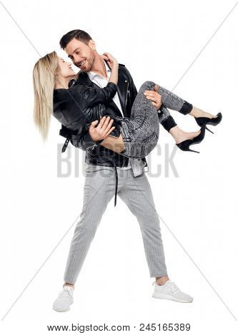 A man is holding a woman in his arms. Smiling couple front view. The guy is wearing his girlfriend in his arms. Isolated on white background. A stylish rocker in pants holds the lover in his arms