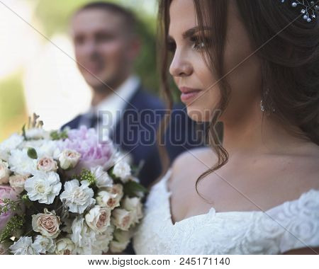 Portrait Of Bride Holds A Wedding Bouquet And Groom At Background. Wedding Couple Just Married. Coup