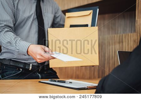 Image Of Businessman Hand Holding Cardboard Box And Sending A Resignation Letter To His Boss, Change