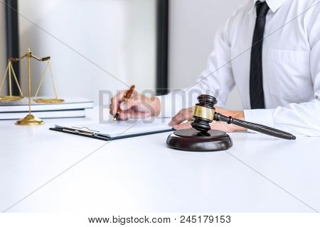 Businessman Or Lawyer Working On A Documents, Judge Gavel With Justice Lawyers At Law Firm In Backgr