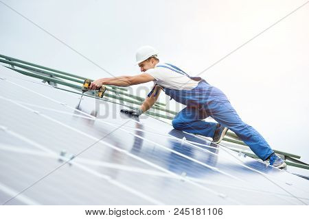 Construction worker connects photo voltaic panel to solar system using screwdriver. Professional installing and construction of solar system, alternative energy and financial investment concept. poster