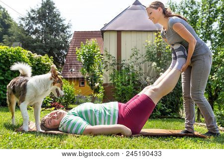 Mentally Disabled Woman Is Getting Trained By A Young Caregiver Or Professional, Laying On A Lawn, D
