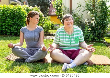 Two Women, One Of Them A Fitness Or Yoga Coach, Are Doing Some Yoga Or Relaxation Exercises, On Woma