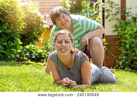 Smiling Mental Disabled Woman And A Friend In The Garden, Sunny Weather