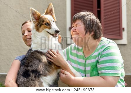 Mental Disabled Woman In Front Of A House Is Holding Her Dog, Female Friend Or Trainer Besides