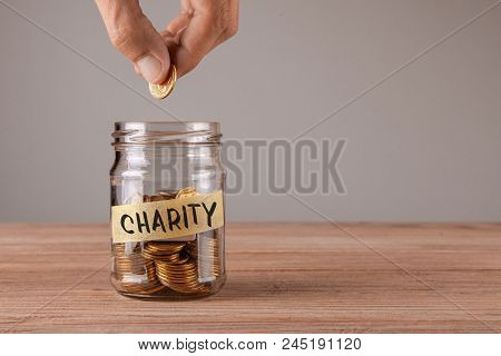 Charity. Glass Jar With Coins And An Inscription Charity. Man Holds  Coin In His Hand