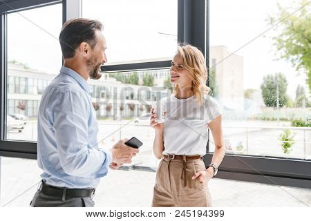Couple of happy colleagues talking while standing at the office window with mobile phone and cup of coffee