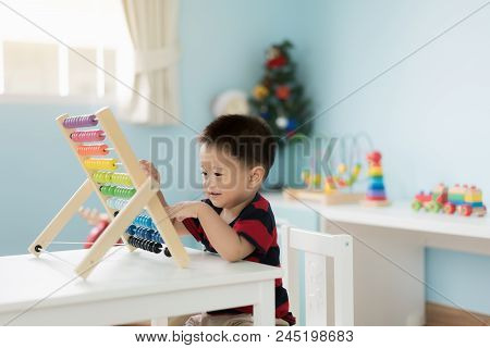 Asian Toddler Baby Boy Learns To Count. Cute Child Playing With Abacus Toy. Little Boy Having Fun In