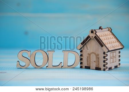 Small Model  Of House With Word Sold On The Blue Background. Real Estate Concept. New House Concept.