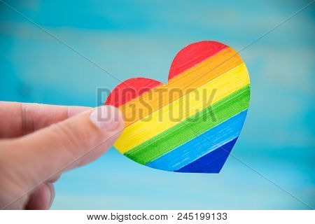 Lgbt Concept. Hand On Blue Background Holding Heart Rainbow Colors