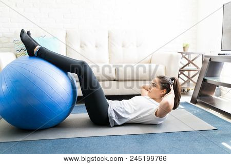 Woman Lying On Yoga Man With Legs On Stability Ball And Hands Behind Head, Doing Sit Up In Living Ro
