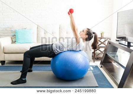 Fit Young Hispanic Woman Leaning Over A Stability Ball And Doing Hands Work Out With Weights