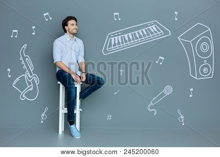 Dreamy Musician. Cheerful Optimistic Talented Musician Sitting Alone And Kindly Smiling While Dreami