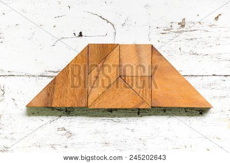 Tangram puzzle in trapezoid or trapezium shape on old white wood background poster