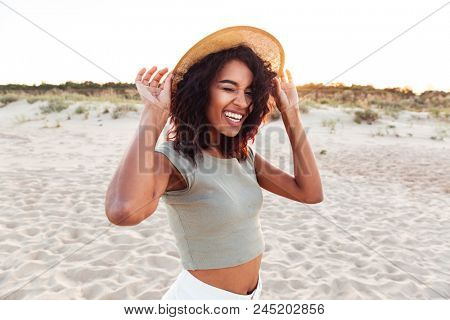 Close up of smiling young african girl in summer hat looking at camera and winking at the beach