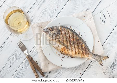 Grilled gilt-head bream on the plate with wine poster