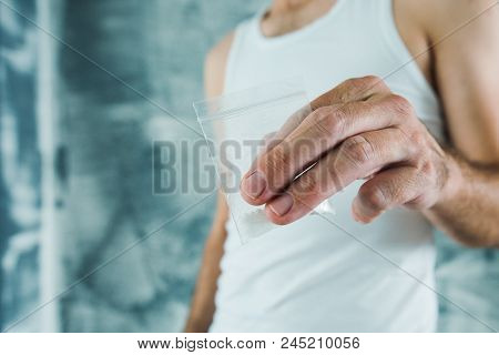 Gang member and drug dealer offering crack cocaine in small plastic bag, close up of hands with selective focus poster