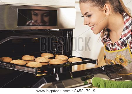 Woman In Kitchen With Hot Baking. Cookies From The Oven.