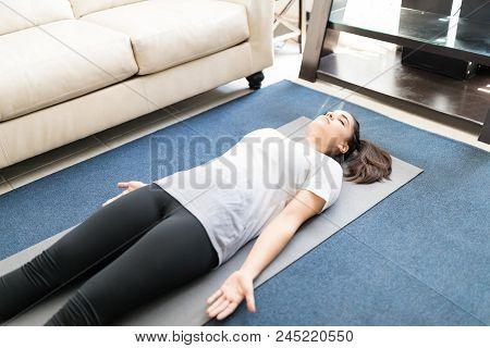 Beautiful Hispanic Woman Practicing Yoga Dead Body Pose Or Savasana Pose Lying On Yoga Mat At Home.